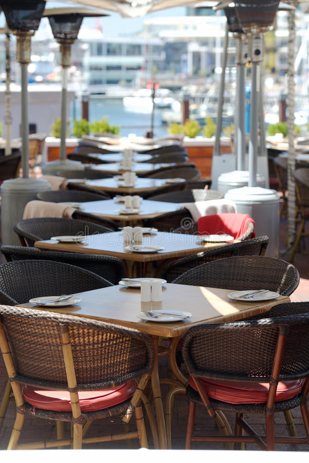 Modern restaurant with the covered tables. Knives and forks, furniture, table napkins. Vertical photo stock photos