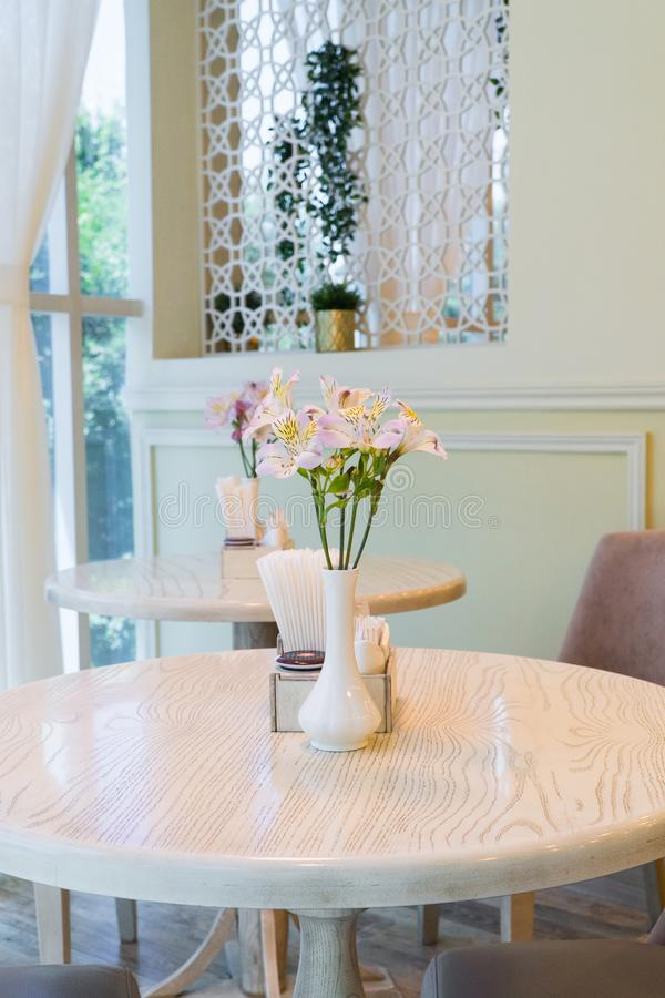 Interior of the cafe. Modern restaurant interior with windows and flowers. cafe room illuminated by sunlight royalty free stock image