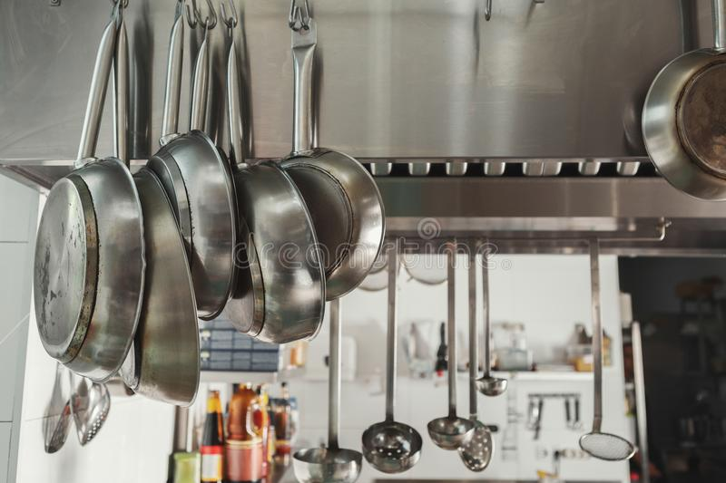 Modern restaurant kitchen interior with frying pans royalty free stock photo