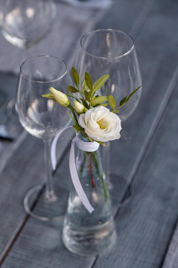 Modern restaurant setting, glass vase with bouquet flowers on table in restaurant. Wine and water glasses stand on wooden table. Concept banquet, birthday stock photography