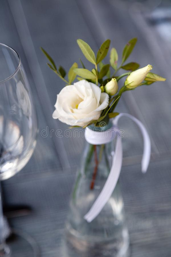 Modern restaurant setting, glass vase with bouquet flowers on table in restaurant. Wine and water glasses stand on wooden table. Concept banquet, birthday royalty free stock photos