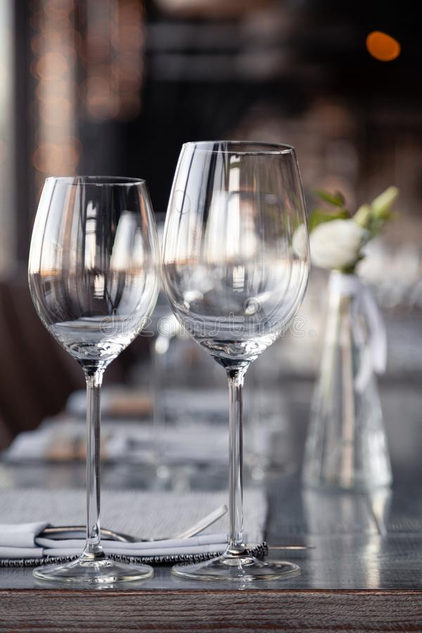 Modern restaurant setting, glass vase with bouquet flowers on table in restaurant. Wine and water glasses stand on wooden table. Concept banquet, birthday royalty free stock photography