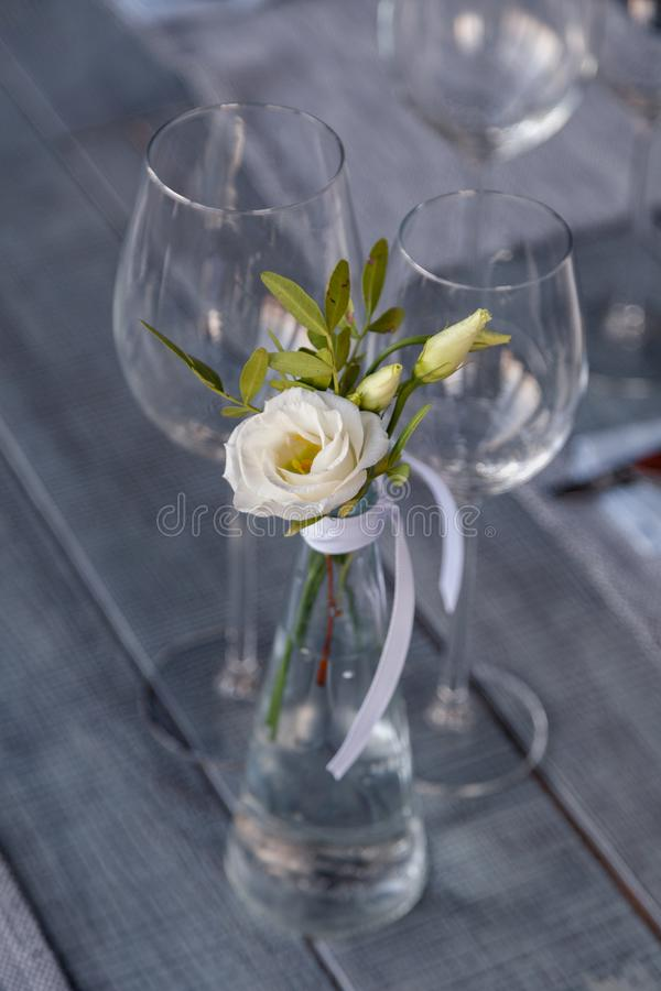 Modern restaurant setting, glass vase with bouquet flowers on table in restaurant. Wine and water glasses stand on wooden table. Concept banquet, birthday stock image