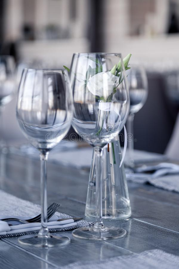 Modern restaurant setting, glass vase with bouquet flowers on table in restaurant. Wine and water glasses stand on wooden table. Concept banquet, birthday stock images