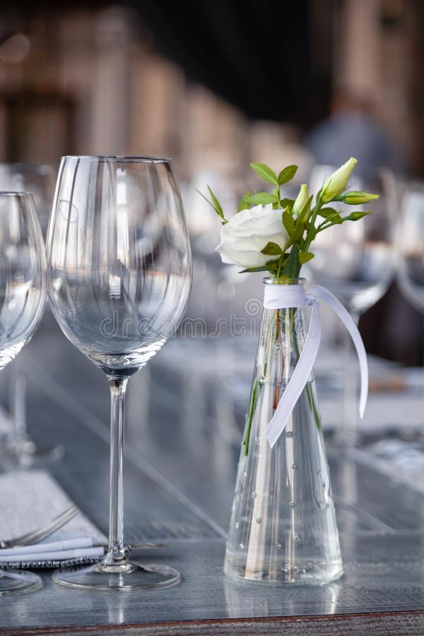 Modern restaurant setting, glass vase with bouquet flowers on table in restaurant. Wine and water glasses stand on wooden table. Concept banquet, birthday royalty free stock images