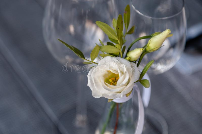 Modern restaurant setting, glass vase with bouquet flowers on table in restaurant. Wine and water glasses stand on wooden table. Concept banquet, birthday stock photos