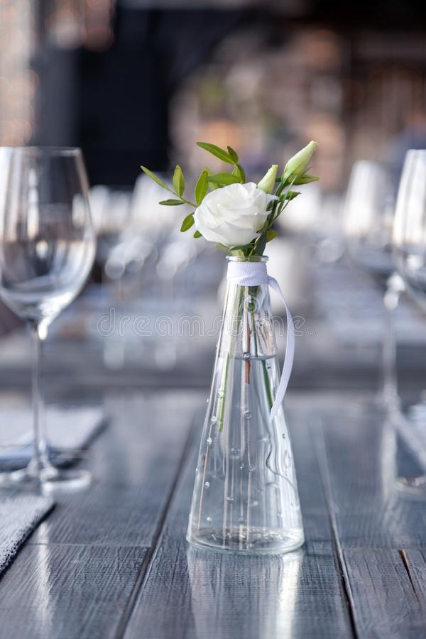Modern restaurant setting, glass vase with bouquet flowers on table in restaurant. Wine and water glasses stand on wooden table. Transparent glass vase with royalty free stock images
