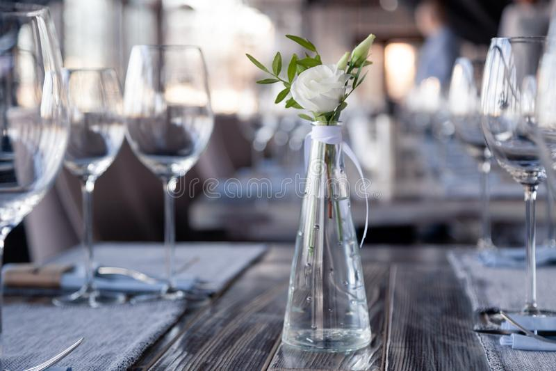 Modern restaurant setting, glass vase with bouquet flowers on table in restaurant. Wine and water glasses stand on wooden table. Transparent glass vase with stock photography