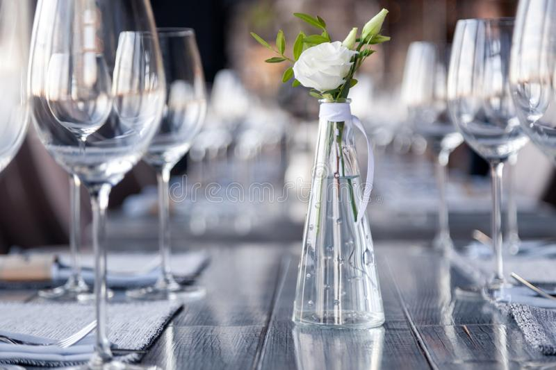 Modern restaurant setting, glass vase with bouquet flowers on table in restaurant. Wine and water glasses stand on wooden table. Transparent glass vase with royalty free stock photography