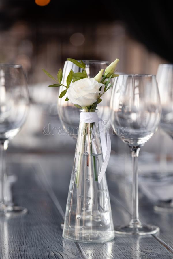 Modern restaurant setting, glass vase with bouquet flowers on table in restaurant. Wine and water glasses stand on wooden table. Transparent glass vase with royalty free stock image
