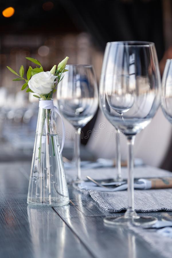 Modern restaurant setting, glass vase with bouquet flowers on table in restaurant. Wine and water glasses stand on wooden table. Transparent glass vase with stock photo
