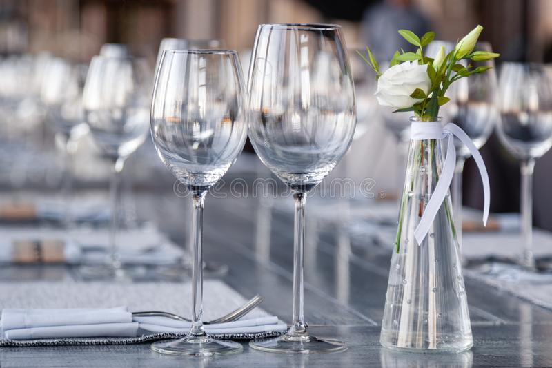 Modern restaurant setting, glass vase with bouquet flowers on table in restaurant. Wine and water glasses stand on wooden table. Transparent glass vase with stock images