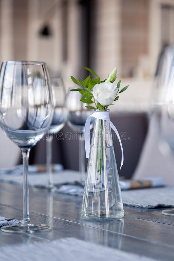 Modern restaurant setting, glass vase with bouquet flowers on table in restaurant. Wine and water glasses stand on wooden table. Transparent glass vase with stock image