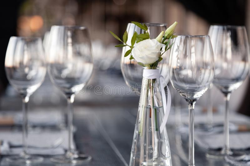 Modern restaurant setting, glass vase with bouquet flowers on table in restaurant. Wine and water glasses stand on wooden table. Transparent glass vase with royalty free stock photo