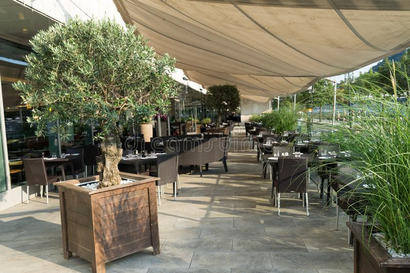 Modern restaurant terrace in the summer with tree in a big pot and canvas to protect from the sun and wicker furniture in a hotel. Chair, bar, dining, outside royalty free stock images