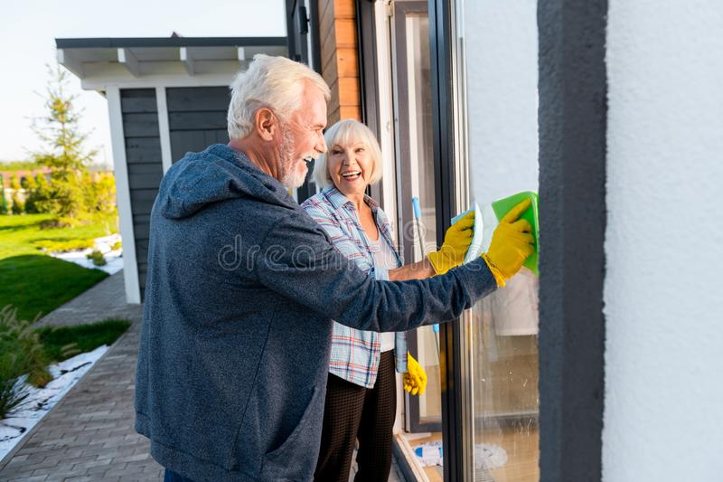 Modern retired couple smiling broadly while cleaning windows outside together stock image