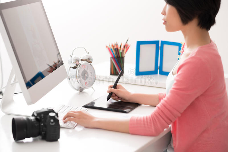 Modern retoucher. Image of a female retoucher at work on the foreground royalty free stock photos