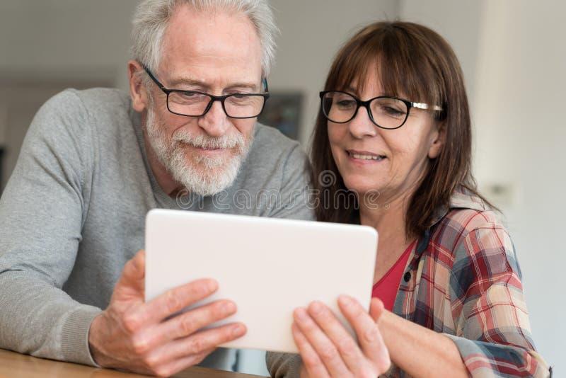Modern rijp paar die tablet gebruiken stock foto's