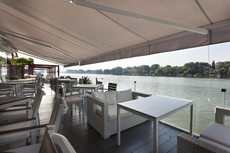 Modern riverside cafe terrace in the morning stock photography