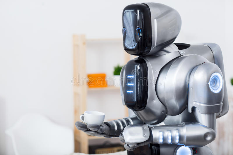 Modern robot holding cup of coffee. Coffee for you. Pleasant big robot holding cup of coffee while looking aside royalty free stock photos