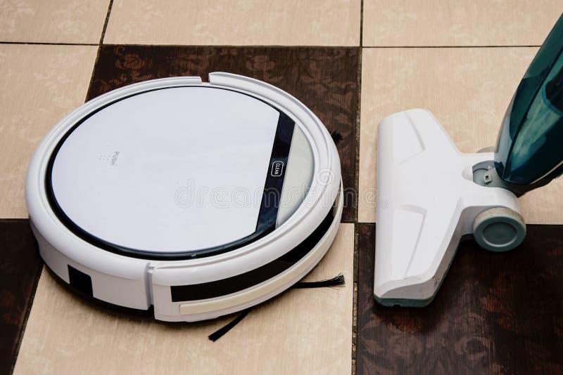 Modern robot vacuum cleaner opposite conventional vacuum cleaner, technology. Modern robot vacuum cleaner in front of a conventional vacuum cleaner, advanced stock images