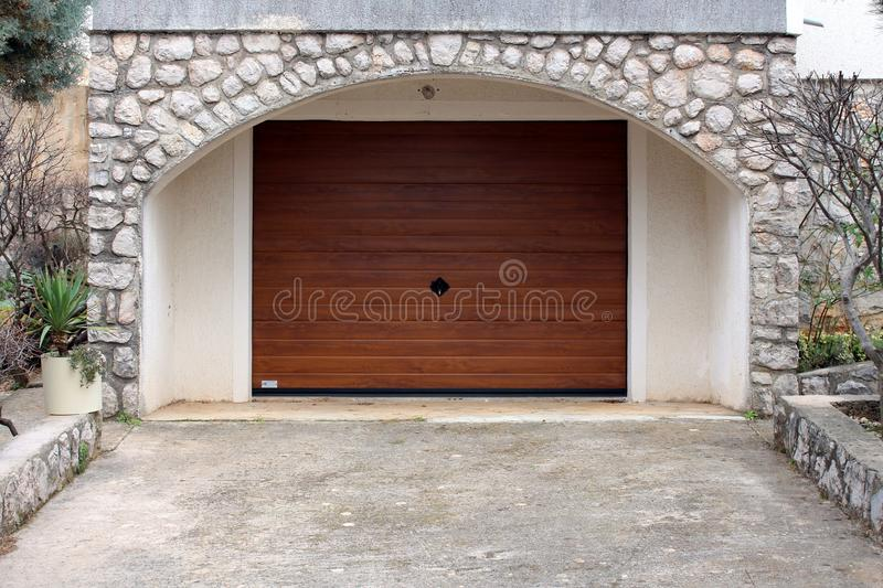 Modern roll up metal garage door with faux wood grain finish. Inside traditional stone wall frame stock image