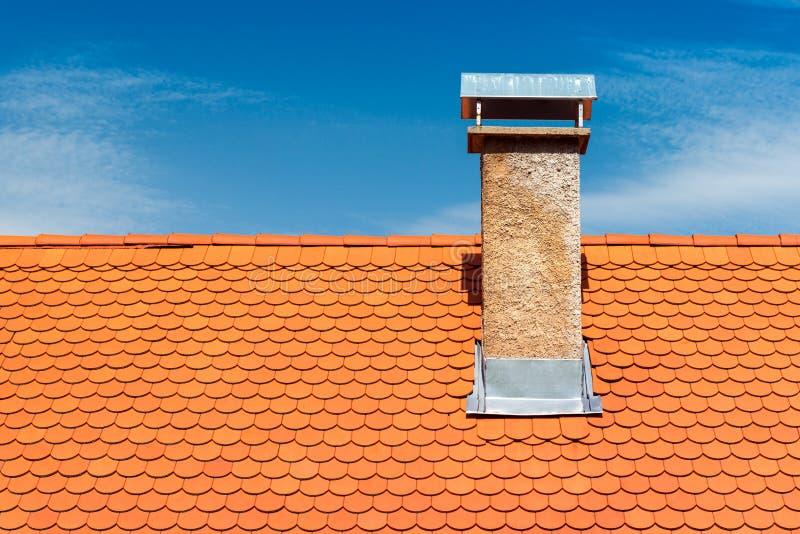 Modern roof with chimney. Orange ceramic tile, shingle royalty free stock images
