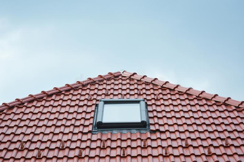 Modern Roof Skylight Window on Red House Clay Ceramic Tiles Roof. Roofing Construction. Modern Roof Skylight Window on Red House Clay Ceramic Tiles Roof stock photo