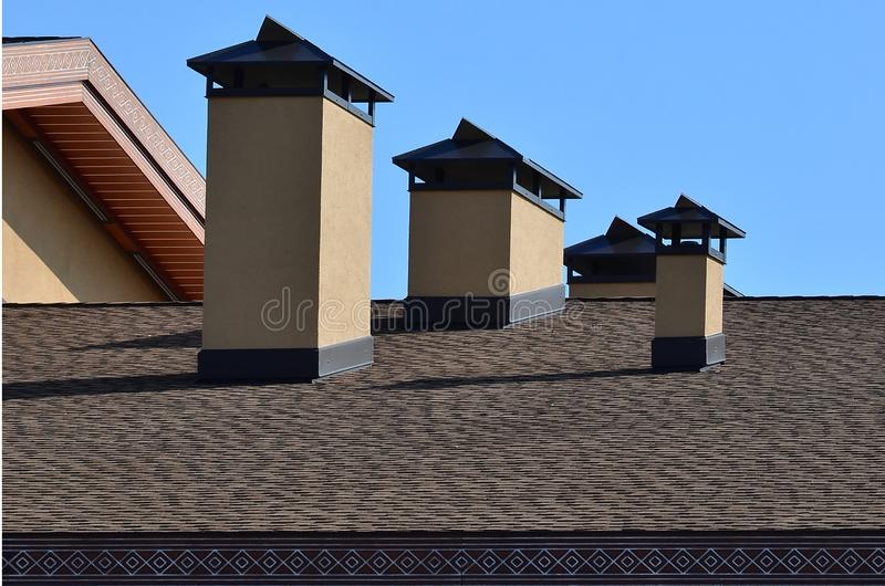 Modern roofing and decoration of chimneys. Flexible bitumen or slate shingles. The absence of corrosion and condensation due to t stock photo