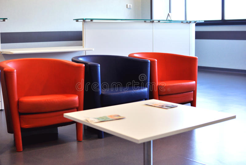 Modern room. Waiting room in a hospital or clinic with three chairs and a table with magazines stock photo