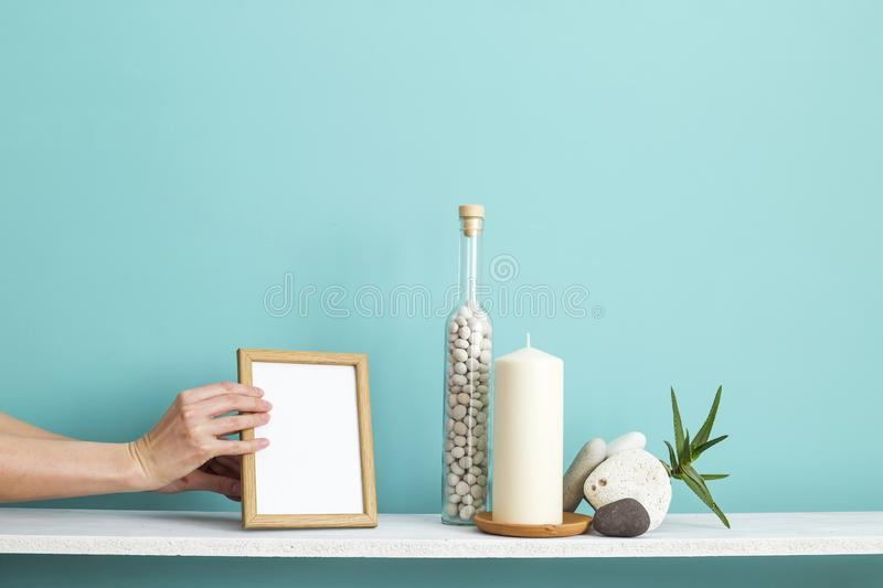 Picture frame mockup. White shelf against pastel turquoise wall with Candle and rocks in bottle. stock photo