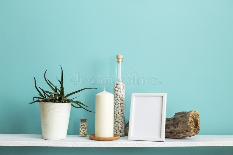 Picture frame mockup. White shelf against pastel turquoise wall with Candle and rocks in bottle. stock photography