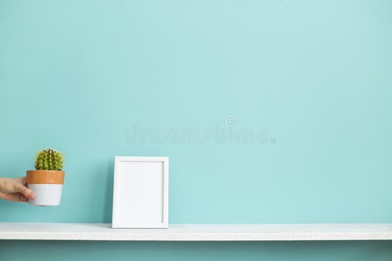 Picture frame mockup. White shelf against pastel turquoise wall with hand putting down potted cactus stock photography