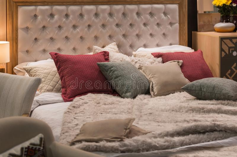 Modern room interior with big bed, cozy room in bright soft colors. Red and gray pillows and a blanket are lying on the bed royalty free stock image
