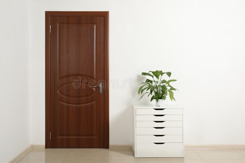 Modern room interior with small cabinet and closed door. stock photo