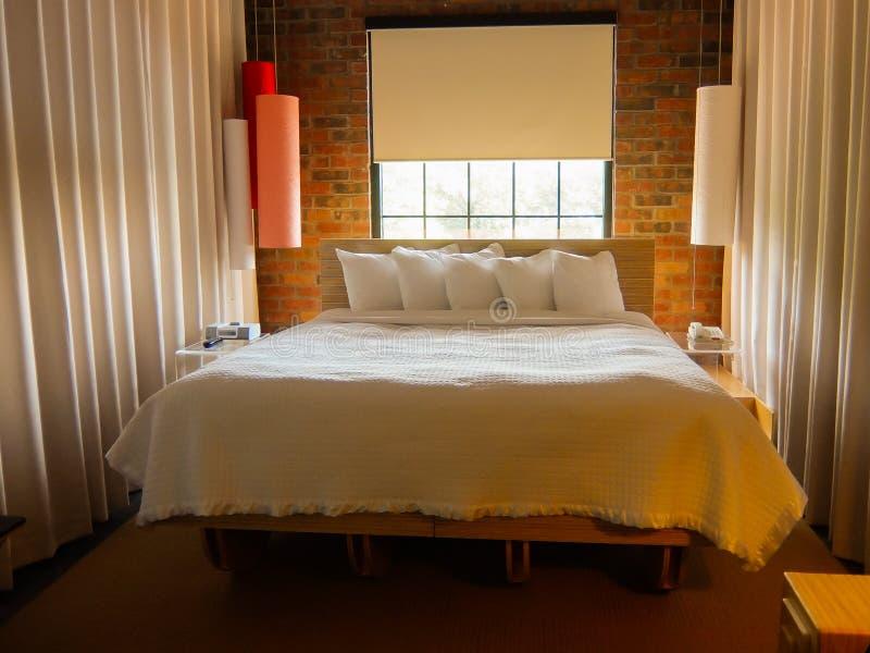 Modern säng i stadslägenhet arkivfoton