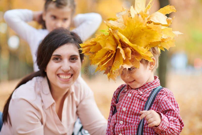 Modern sätter gula stupade sidor på sonhuvudet Den lyckliga familjen är i höststad parkerar Barn och föräldrar Dem posera som ler royaltyfri foto