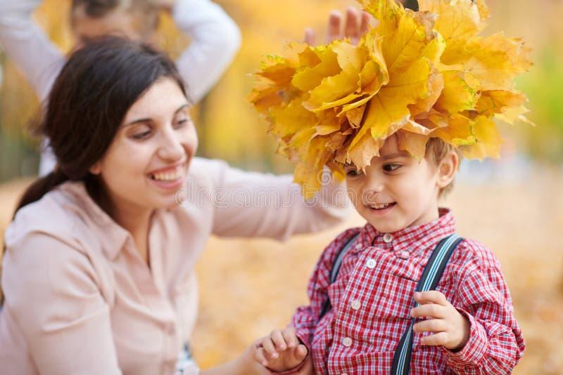 Modern sätter gula stupade sidor på sonhuvudet Den lyckliga familjen är i höststad parkerar Barn och föräldrar Dem posera som ler royaltyfri fotografi