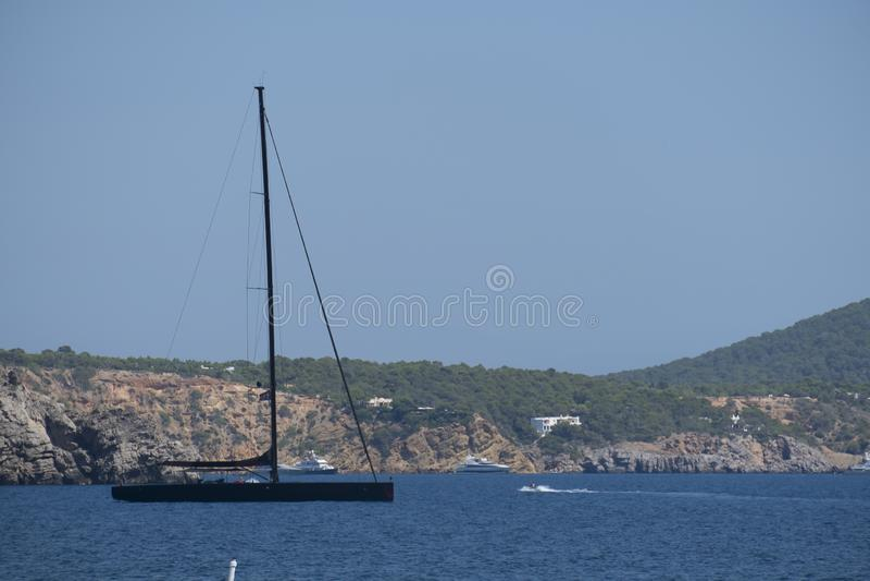 Modern black sail boat at sea. Modern sail boat sailing on calm blue water at the Spanish Island Ibiza in the Mediterranean stock photos