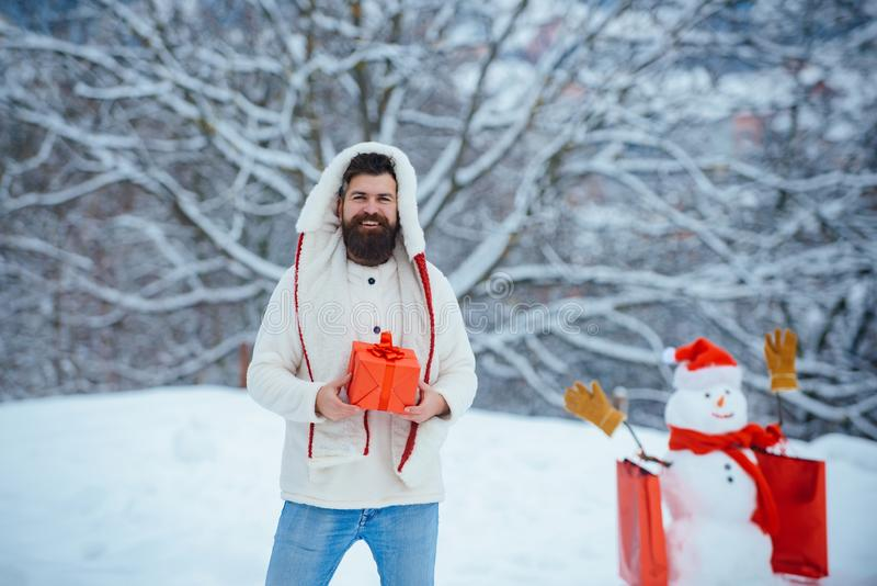 Modern Santa. Santa drunk at home. Handsome Santa Claus. Funny Santa man posing with red gift box on winter weather. royalty free stock photography
