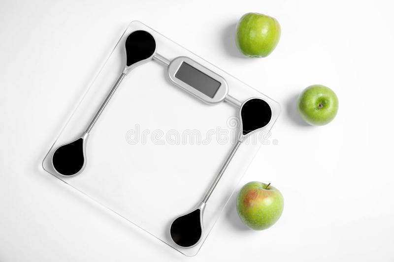 Modern scales and apples on white background royalty free stock images