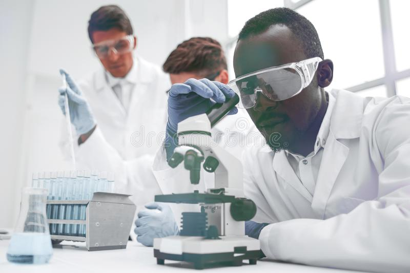 Modern scientist looking through a microscope royalty free stock image
