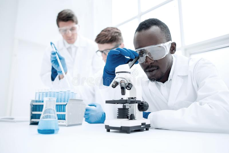Modern scientist looking through a microscope stock photography