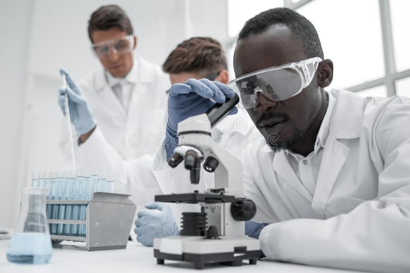 Modern scientist looking through a microscope stock image