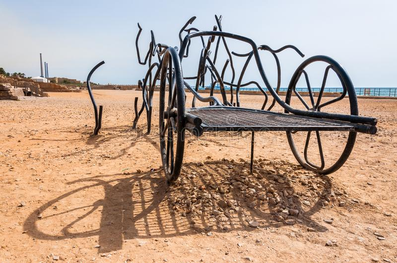 Modern sculpture of Roman Horse Chariot made of black bent forged metal stand on ancient Caesarea beach where long time ago was royalty free stock photography
