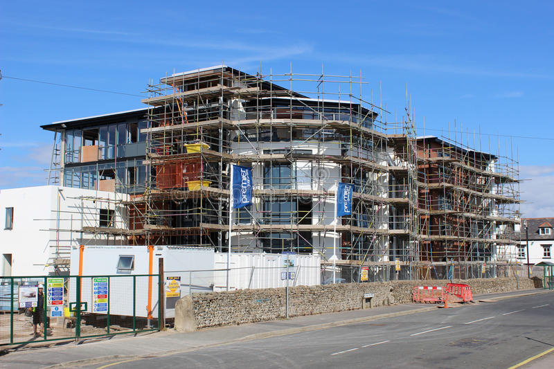 Modern seaside apartments under construction. Large block of modern apartments under construction at the seaside with scaffolding surrounding them during the stock images