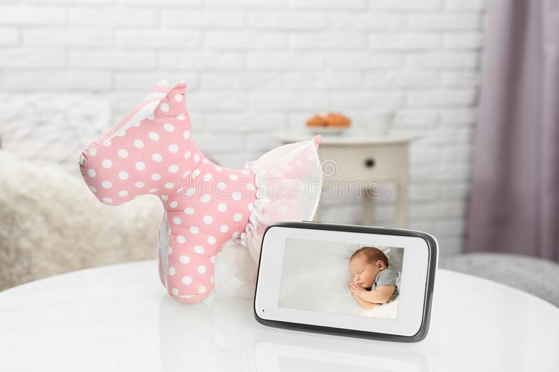 Modern security CCTV monitor with baby`s image on table. Space for text stock photos
