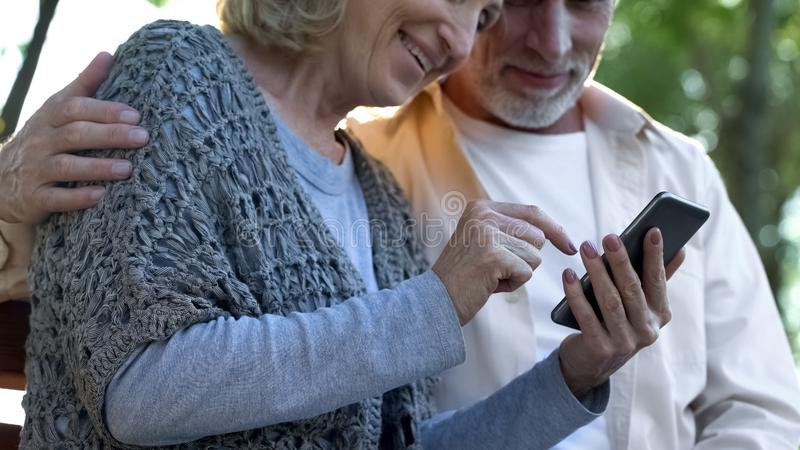 Modern senior couple easily using mobile phone, looking through photos online. Stock photo royalty free stock image
