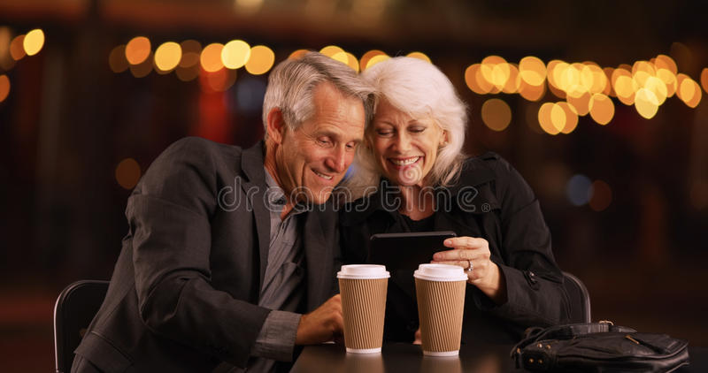 Modern Senior couple looking at photos on their smartphone royalty free stock photos
