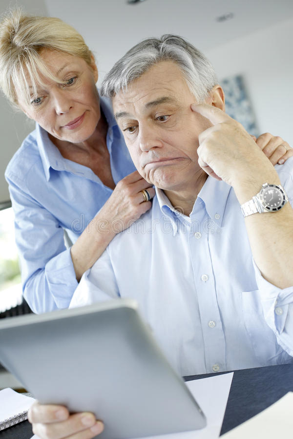 Modern senior couple making tax declaration online. Senior couple trying to figure out tax declaration royalty free stock images